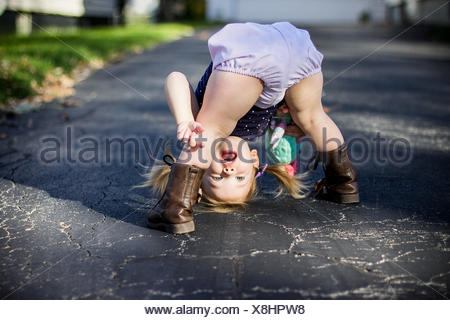 Girl bending over and looking through her legs upside down - Stock Photo