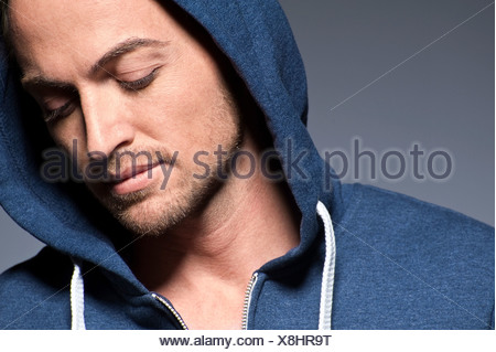 Young man wearing hood and looking down - Stock Photo