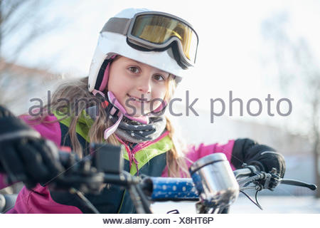 Portrait of girl wearing helmet and goggles - Stock Photo