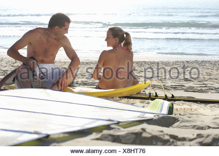 Young couple assembling windsurfer on sandy beach smiling - Stock Photo