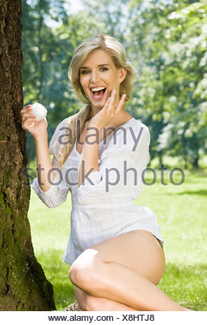 young woman creaming face in garden - Stock Photo