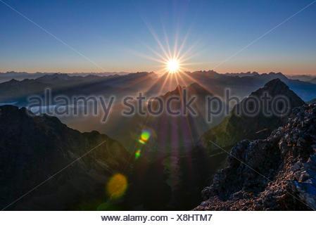 Sunrise and sunrays over the Karwendel with Arnspitzen in the middle ground, foreground Wetterstein Range, view of Schüsselkarspitze, - Stock Photo