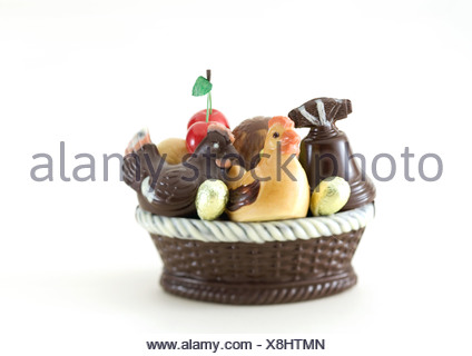 Basket of chocolate chickens, eggs and bell - Stock Photo