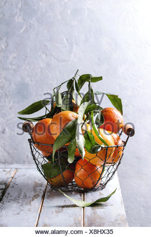 Ripe organic clementines or tangerines with leaves in basket standing on white wooden plank table with gray wall as background. Rustic style. Healthy  - Stock Photo