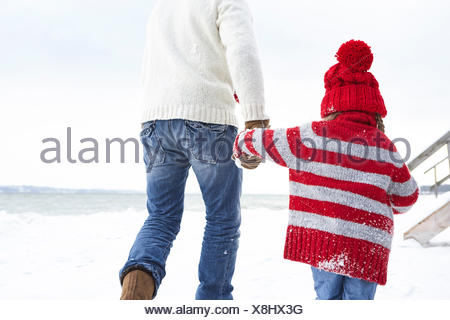 Father and daughter walking in the snow, rear view - Stock Photo