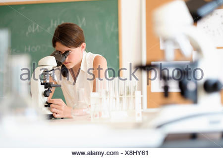 Girl (10-11) using microscope - Stock Photo