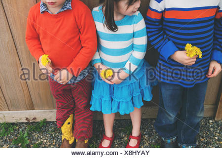 Three children standing in a row, holding flowers - Stock Photo