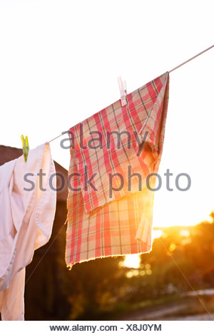 Laundry drying in evening sun - Stock Photo