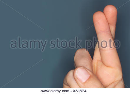 Close-up of hand with fingers crossed - Stock Photo