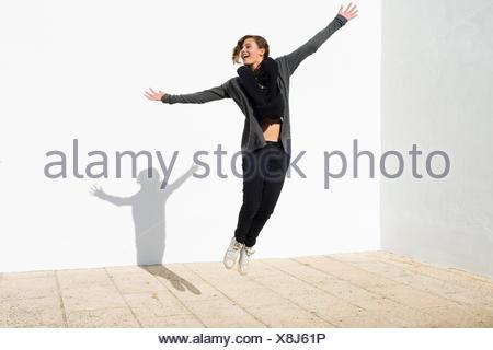 Spain, Andalusia, Ronda, Teenage girl (14-15) jumping - Stock Photo
