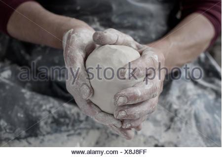 Close-up of female potter's hand holding clay, Bavaria, Germany - Stock Photo