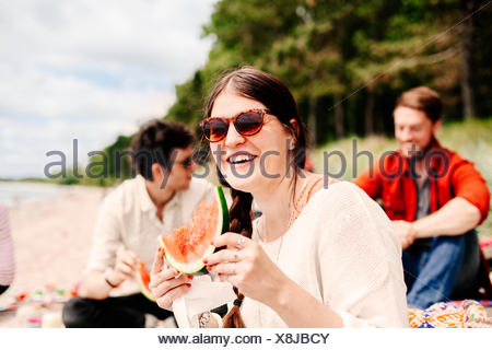 Young woman eating watermelon at beach - Stock Photo