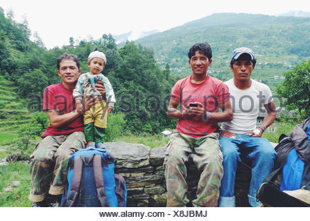 Three men sitting on a wall with a baby boy, Nepal - Stock Photo