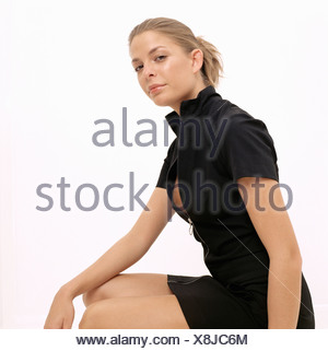 Young woman in black dress sitting - Stock Photo
