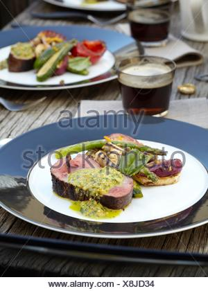 Close up of chimichurri Beef with barbecued salad outdoors on wooden garden table - Stock Photo