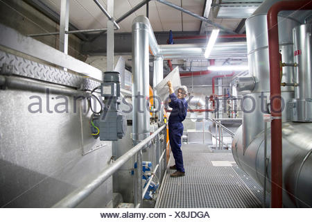 Engineer removing cover from equipment in power station - Stock Photo