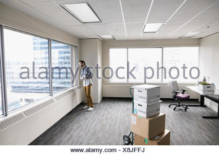 Pensive businessman looking out urban window of new office - Stock Photo