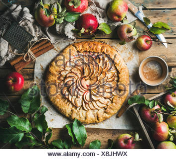 Apple crostata pie with cinnamon served with fresh garden apples with leaves on rustic wooden background, top view, horizontal c - Stock Photo