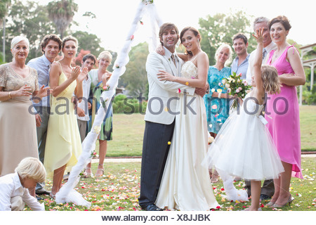Guests with bride and groom smiling - Stock Photo