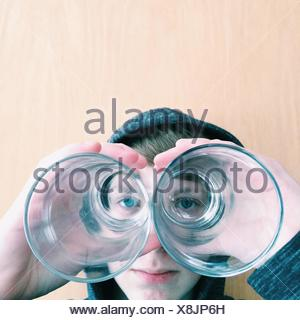 Boy looking through the bottom of two drinking glasses - Stock Photo
