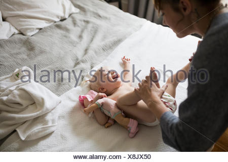 Mother changing baby daughter - Stock Photo