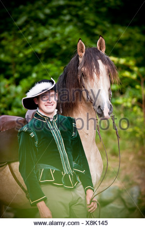 Frederiksborger. Rider in historic costume standing next to a dun stallion - Stock Photo