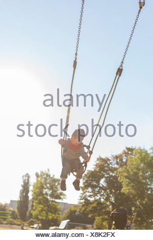 Sweden, Stockholm, Boy (12-17 months) swinging outdoors - Stock Photo