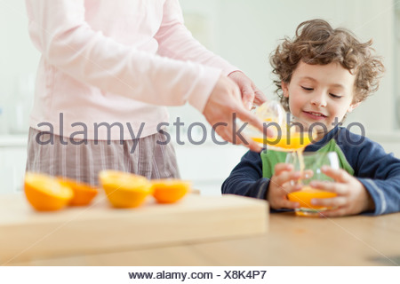 Mother pouring orange juice for son - Stock Photo