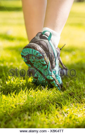 Woman in running shoes stepping on grass - Stock Photo