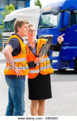 Logistics - proud driver or forwarder and female coworker with tablet computer, in front of trucks and trailers, on a transshipment point, its a good and successful team - Stock Photo