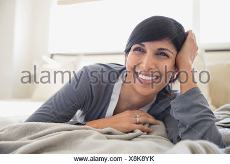 Happy mature woman looking away in bed - Stock Photo