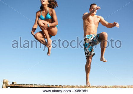 Young couple jumping of dock - Stock Photo