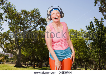 Senior adult woman exercising in park - Stock Photo