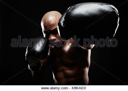 Boxer with black boxing gloves punching towards camera - Stock Photo