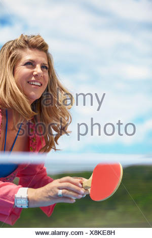 Smiling older woman playing table tennis - Stock Photo