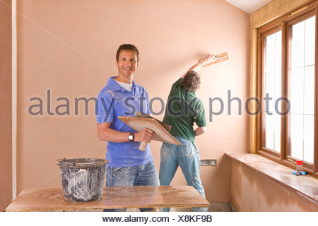 Men plastering wall in house - Stock Photo