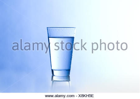 Water glass with a blue background - Stock Photo