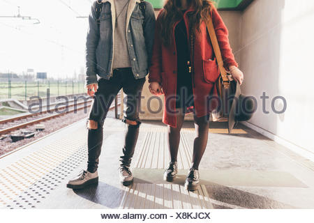 Portrait of young couple on train platform, low section - Stock Photo