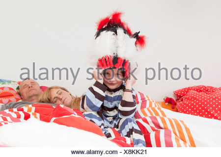 Boy wearing war bonnet in parents' bed - Stock Photo