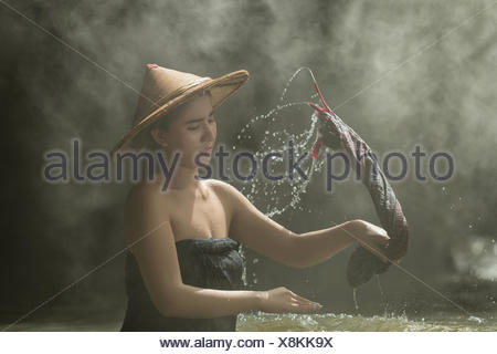Woman washing clothes in the river, Thailand - Stock Photo