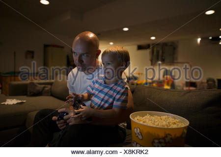Father and son playing video game game room - Stock Photo