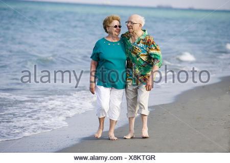 Senior couple strolling along the beach - Stock Photo