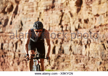 Male triathlete cyclist cycling along sunny rocks - Stock Photo