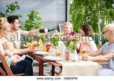 Three generation family having lunch and pouring wine on patio table - Stock Photo