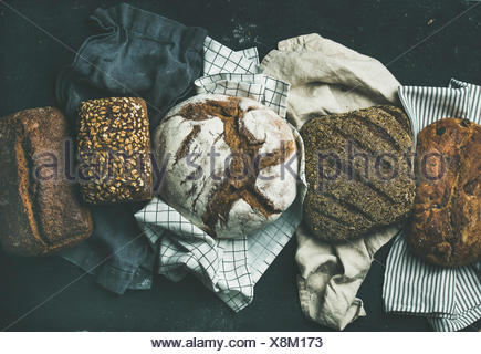 Various bread selection flat-lay. Top view of Rye, wheat and multigrain rustic bread loaves over black background - Stock Photo
