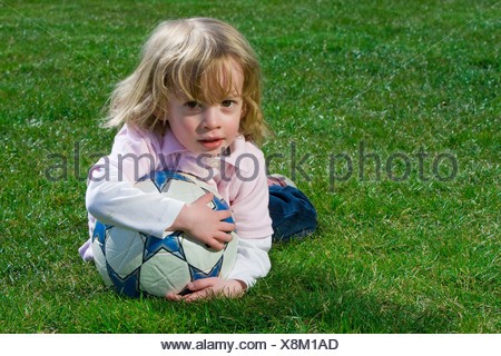 Cute young caucasian boy playing football or soccer outdoors - Stock Photo