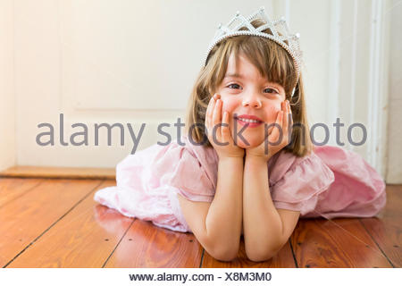 Portrait of smiling little girl dressed up as a princess lying on wooden floor - Stock Photo
