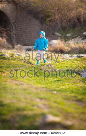 Girl (4-5) running by river - Stock Photo