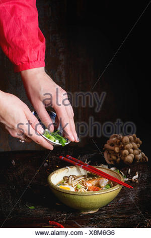 Female hand in red shirt sprinkle with sliced spring onion asian ramen soup with shrimp, noodles, sliced egg and mushrooms, serv - Stock Photo