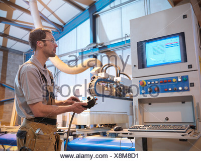 Woodworker with cutting machine - Stock Photo